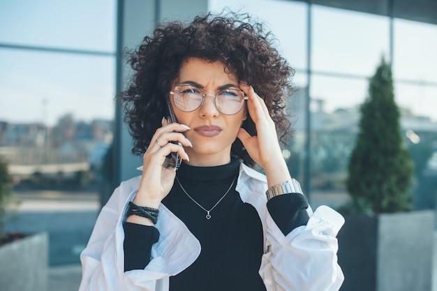 Mulher caucasiana séria com cabelo encaracolado e óculos, olhando para a câmera enquanto conversa do lado de fora por telefone