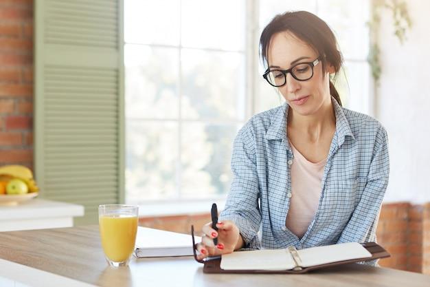 Mulher caucasiana séria usa óculos e camisa, cria o menu enquanto se senta sobre o interior da cozinha.