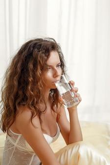 Mulher caucasiana, sexy e cacheada, sentada em uma cama matinal segurando um copo d'água