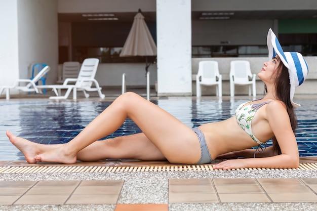 Mulher caucasiana sexy elegante de biquíni posando perto da piscina.