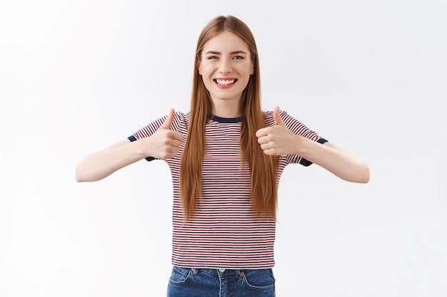 Mulher caucasiana simpática, alegre e bonita em uma camiseta listrada, mostrando resposta positiva, polegar para cima e sorrindo concordando, acenando com a cabeça em aceitação, como uma ideia incrível, fundo branco de pé