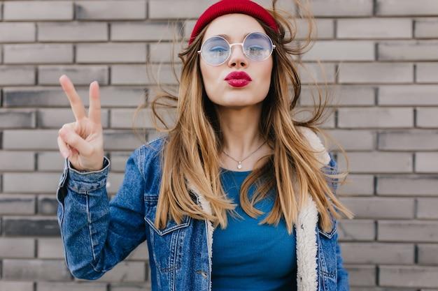 Mulher caucasiana sonhadora em roupas da moda na parede de tijolos