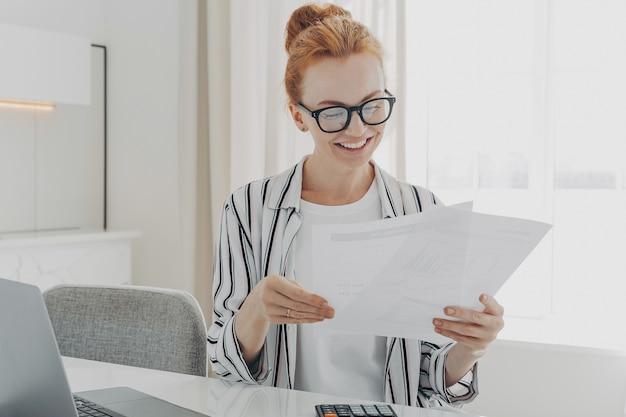 Mulher caucasiana sorridente e feliz lendo boas notícias em documentos financeiros enquanto gerencia o orçamento familiar