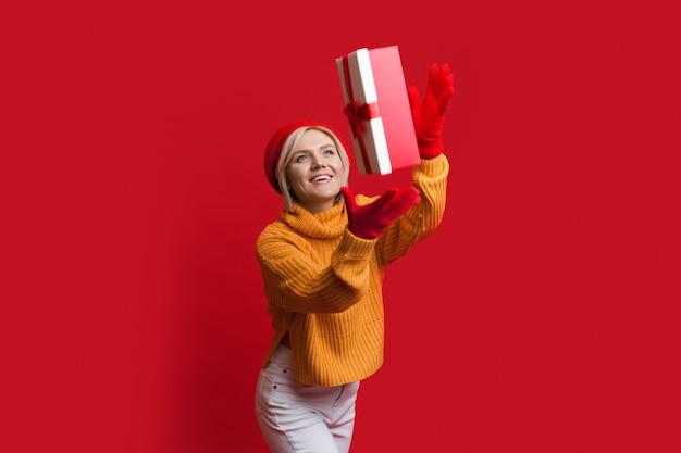 Mulher caucasiana sorridente está usando luvas e chapéu em uma parede vermelha enquanto pega uma caixa de presente