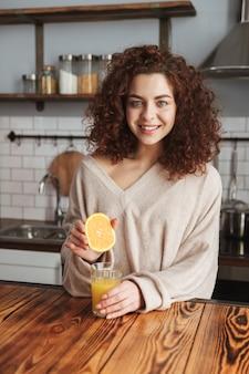 Mulher caucasiana sorridente fazendo e bebendo suco de laranja fresco enquanto toma o café da manhã no interior da cozinha em casa
