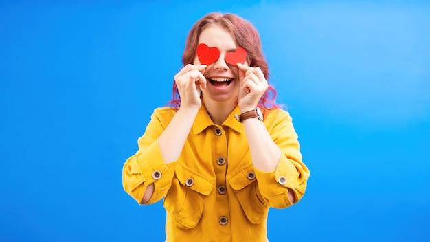 Mulher caucasiana sorridente feliz com dois corações vermelhos