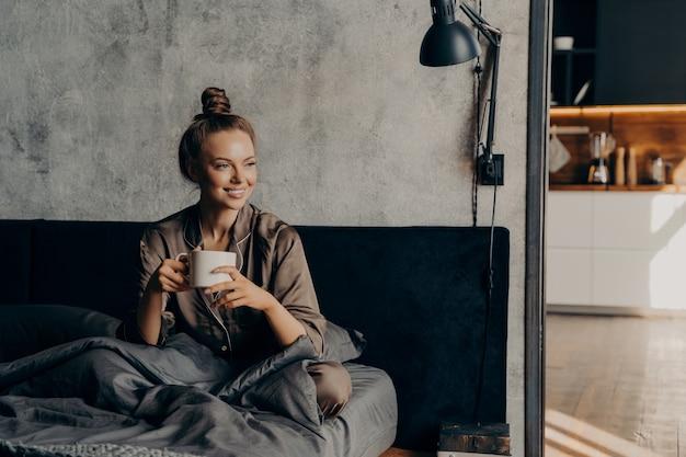 Mulher caucasiana sorridente feliz de pijama, desfrutando de uma xícara de café matinal enquanto está sentada na cama, depois de acordar antes de iniciar seu dia agitado de trabalho, relaxando no quarto de um apartamento contemporâneo ou hotel