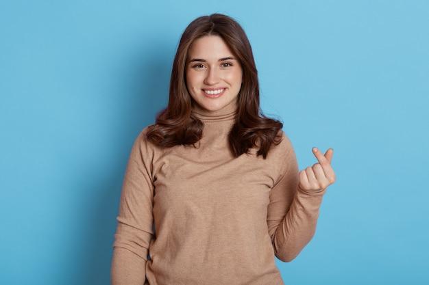 Mulher caucasiana sorridente feliz faz sinal de mão coreana, expressa amor, faz como gesto, vestida com gola rulê bege casual, isolada na parede bege.