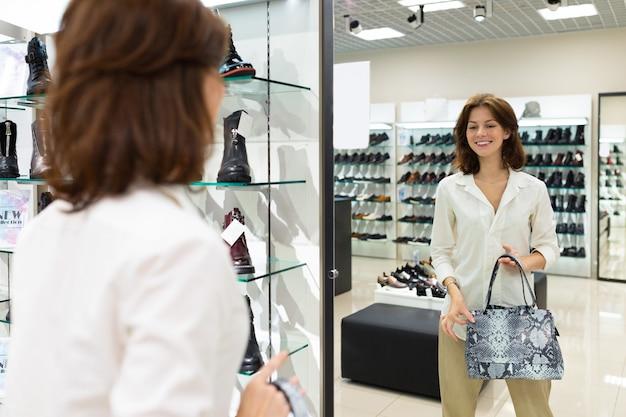Mulher caucasiana sorridente se olha no espelho, segurando a bolsa de couro azul na mão.