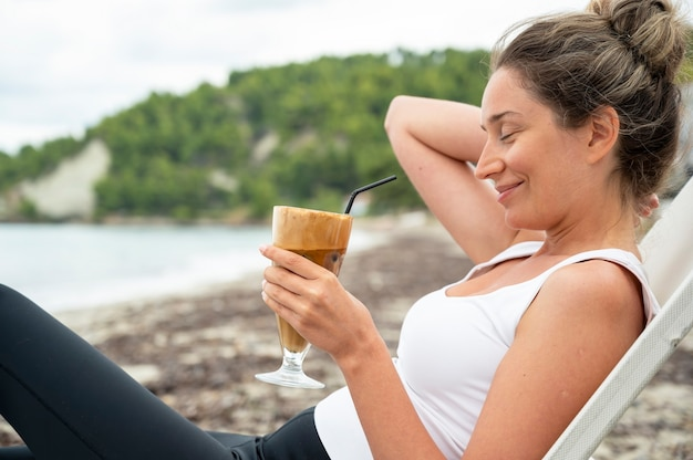 Mulher caucasiana sorridente segurando uma bebida de café em uma praia com espuma e canudo com colinas