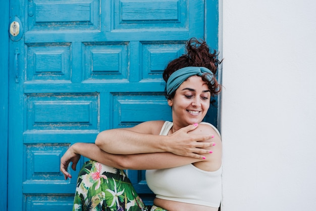 Mulher caucasiana sorridente, sentado em frente a uma porta azul durante o verão. estilo de vida ao ar livre