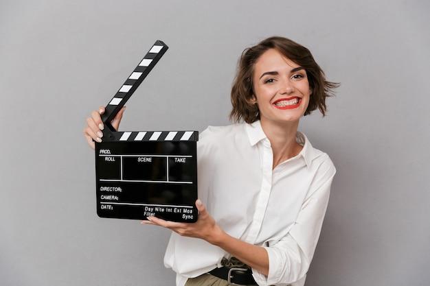 Mulher caucasiana, sorrindo e segurando uma claquete preta, isolada sobre uma parede cinza