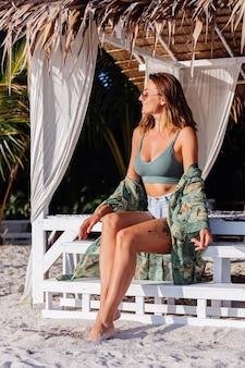 Mulher caucasiana tatuada em shorts jeans e top verde moderno na praia