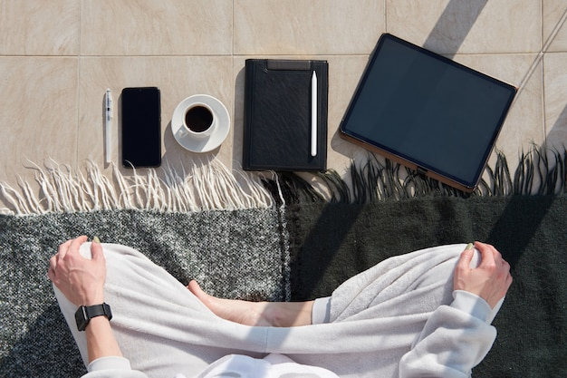 Mulher caucasiana tem meditação matinal de pijama antes de trabalhar no tablet digital como freelancer