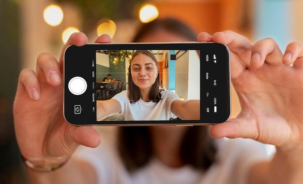 Mulher caucasiana tirando uma selfie com seu smartphone
