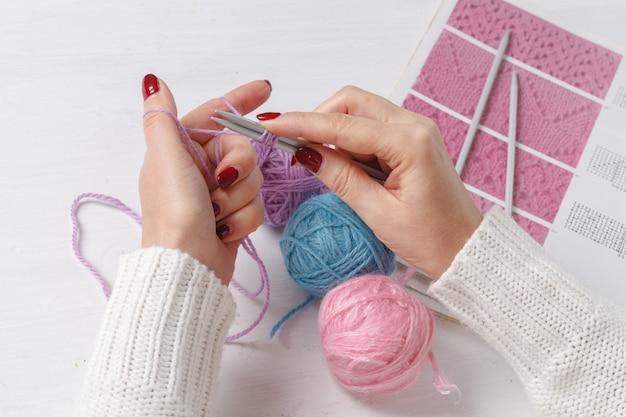 Mulher caucasiana tricota roupas de lã