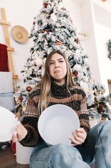 Mulher caucasiana triste segurando um grande presente de natal vazio enquanto está sentado no chão em casa perto da árvore de natal.