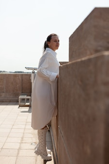 Mulher caucasiana turista em pé no telhado da torre apreciando