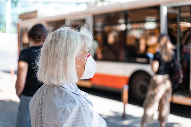 Mulher caucasiana usando máscara de proteção na estação de trem pública
