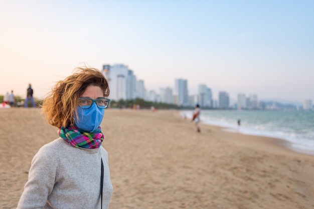 Mulher caucasiana, usando máscara sanitária ao ar livre na praia de nha trang, famosa detenção de viagens no vietnã. turista com proteção de máscara médica contra risco de novo vírus de corona covid-19 na ásia