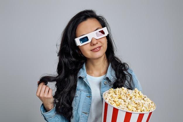 Mulher caucasiana, usando óculos 3d vermelho-azul e segurando o balde de pipoca na cinza
