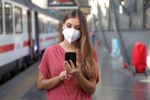 Mulher caucasiana usando telefone inteligente na estação de trem