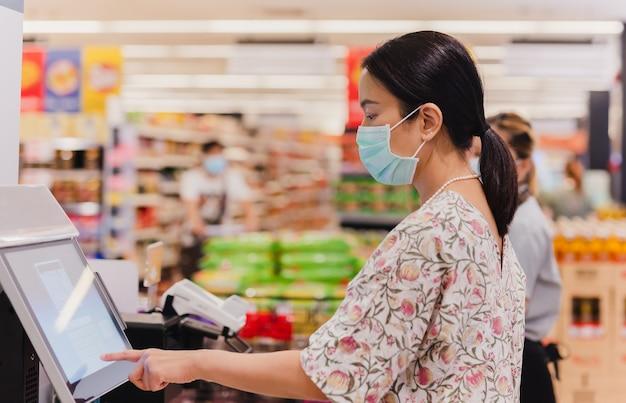 Mulher caucasiana usando um balcão self-checkout em um supermercado de mercearia