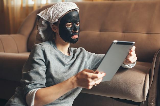 Mulher caucasiana usando uma máscara preta está sentada em casa durante a quarentena e usando um tablet
