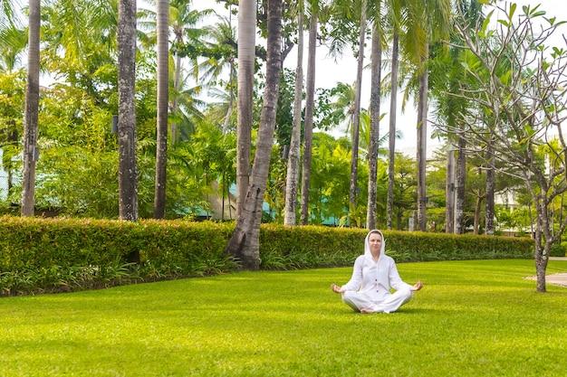 Mulher caucasiana, vestindo roupas brancas praticando ioga em um gramado verde