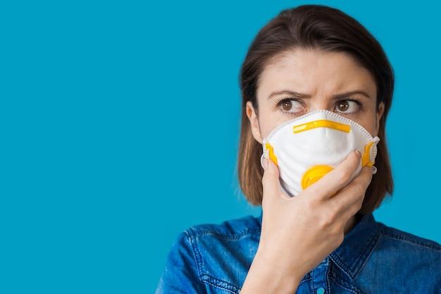 Mulher caucasiana, vestindo roupas jeans, segurando uma máscara protetora no rosto enquanto olha para o espaço azul livre perto dela
