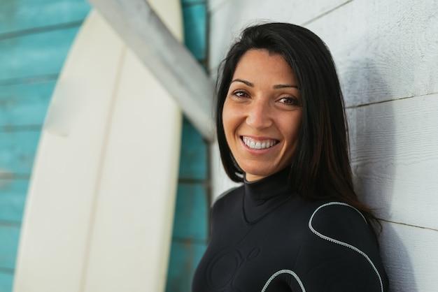 Mulher caucasiana, vestindo um terno de surfe e uma prancha de surf, sorrindo alegremente