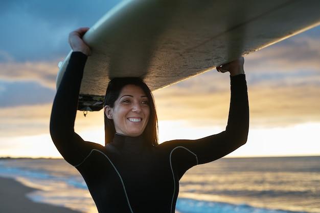 Mulher caucasiana, vestindo um terno de surfe e uma prancha de surfe, sorrindo alegremente