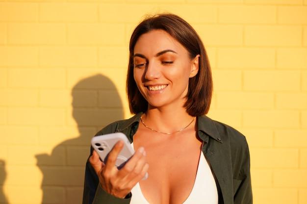 Mulher caucasiana, vestindo uma camisa ao pôr do sol na parede de tijolo amarelo ao ar livre, olhar positivo para a tela do celular com um sorriso
