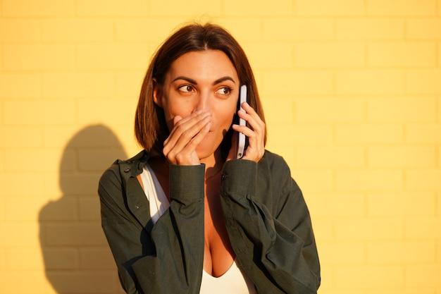 Mulher caucasiana, vestindo uma camisa ao pôr do sol na parede de tijolo amarelo, conversas positivas ao ar livre no celular, contando uma boca secreta com a mão