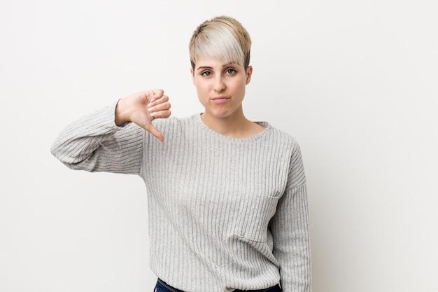 Mulher caucasiano curvy nova isolada no branco que mostra um gesto do desagrado, polegares para baixo.