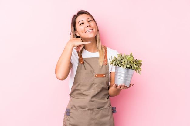 Mulher caucasiano do jardineiro novo isolada mostrando um gesto de chamada de telefone móvel com dedos.