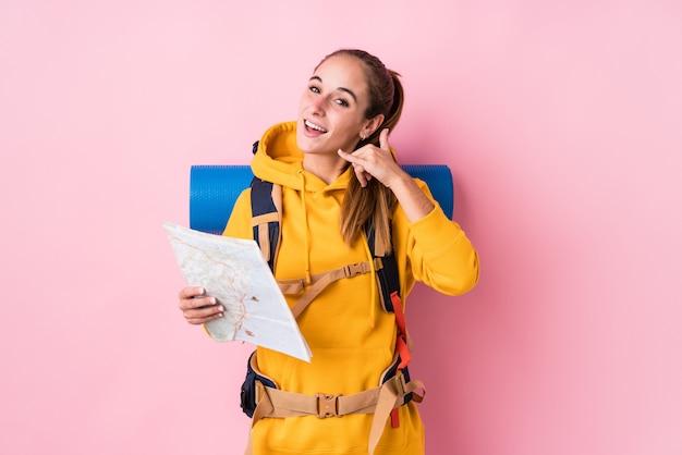 Mulher caucasiano do jovem viajante isolada mostrando um gesto de chamada de telefone móvel com os dedos.