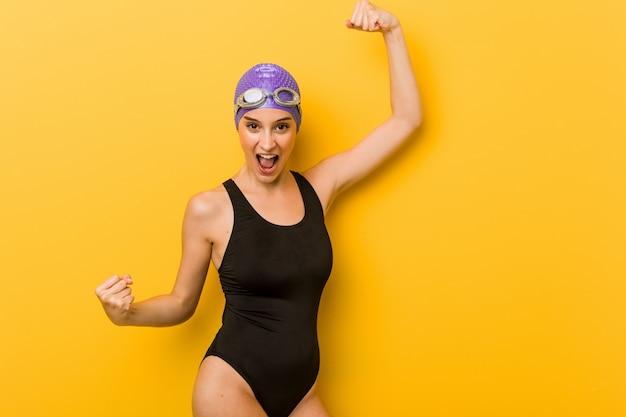 Mulher caucasiano do nadador novo que levanta o punho após uma vitória, conceito do vencedor.