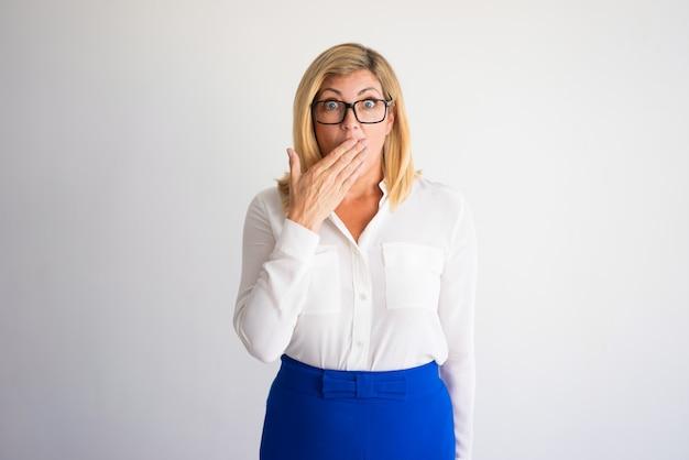 Mulher caucasiano madura chocada com os vidros que cobrem a boca com a mão.