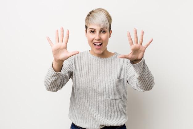 Mulher caucasiano nova isolada no fundo branco que mostra o número dez com mãos.