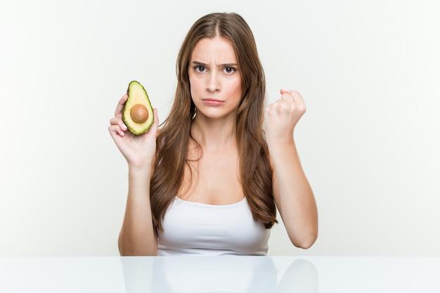 Mulher caucasiano nova que guarda um abacate que mostra o punho, expressão facial agressiva.