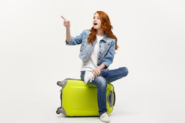 Mulher caucasiano nova que senta-se em uma mala de viagem e que aponta a direção aonde ir.