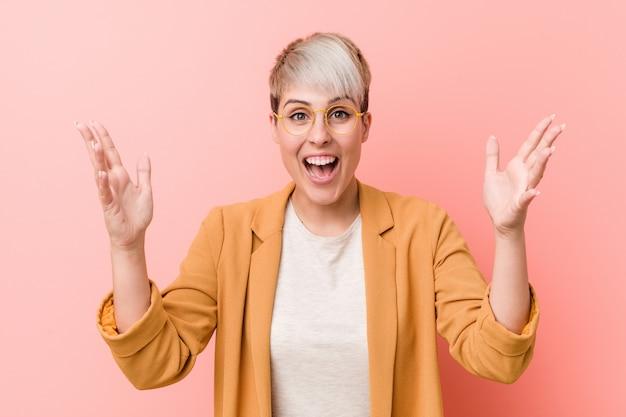 Mulher caucasiano nova que veste uma roupa ocasional do negócio que recebe uma surpresa agradável, entusiasmado e levantando as mãos.