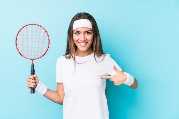 Mulher caucasic nova que joga a pessoa isolada badminton que aponta à mão a um espaço da cópia da camisa, orgulhoso e confiante
