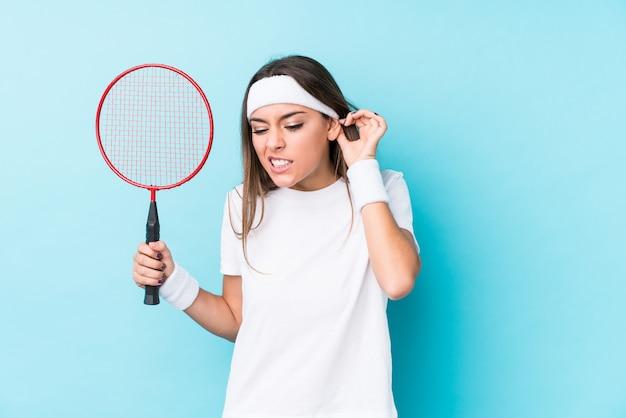 Mulher caucasic nova que joga o badminton isolado cobrindo as orelhas com as mãos.