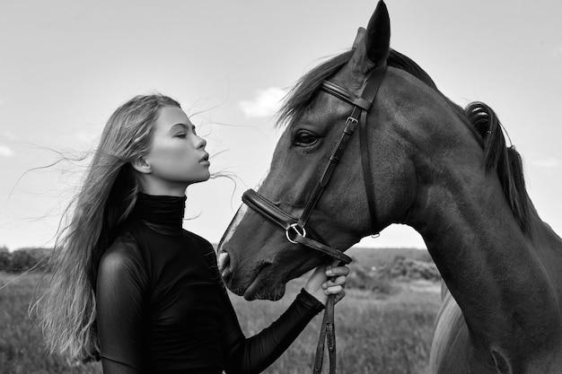 Mulher cavaleira fica ao lado do cavalo no campo. o retrato da moda de uma mulher e as éguas são cavalos na vila na grama. mulher loira segurando um cavalo