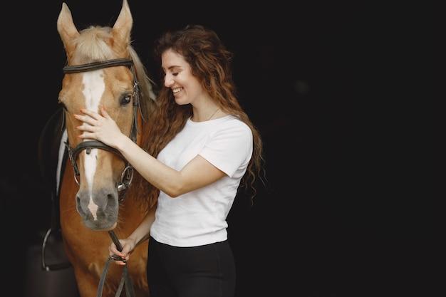 Mulher cavaleiro conversando com seu cavalo em um estábulo. mulher tem cabelo comprido e camiseta branca. o fundo é escuro e preto.