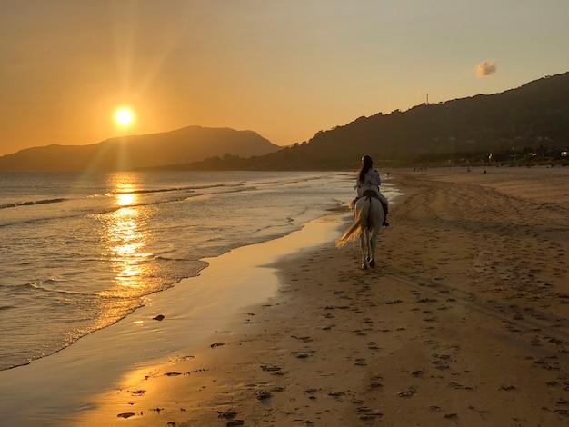 Mulher cavalgando ao pôr do sol na praia