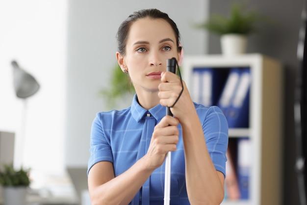 Mulher cega com olhar ausente olha para longe e segura um emprego de bastão para cegos