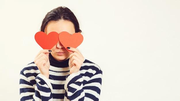 Mulher cega pelo grande amor. jovem fêmea segurando corações vermelhos sobre os olhos e sorrindo. seja meu namorado.